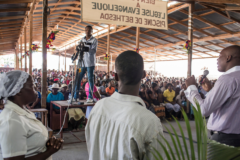 Worshipers at L'Eglise Evangelique Piscine de Bethesda, the church of televangelist Marcorel Zidor give testimonials of their miracle medical cures on Saturday, December 20, 2014 in Port-au-Prince, Haiti. Pastor Zidor attracts a large audience with his emotional services and medical miracles. The man on the right claims that Pastor Zidor cured him of HIV.