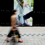 A woman walks past an outdoor advertisement in Myeondong, a popular shopping district in Seoul, South Korea.