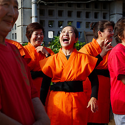 Nobuko Oshiro, 65 and center, leads a group of women in the end-of-summer performances that are part of an annual festival in Ogimi, Okinawa. Residents agree that maintaining strong social health is as important as maintaining good physical health.