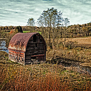 An old dilapidated barn hanging over the edge of the river along Route 79 on the way to Ithaca, NY.