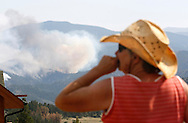 Jessie Couillard watches the High Park fire only a few miles from her home in Glacier View Meadows northwest of Fort Collins, Colorado June 18, 2012.  The fire has charred more than 85 square miles (200 square km) and sent a plume of smoke billowing thousands of feet into the air. Coulliard's home was under a pre-evacuation notice. REUTERS/Rick Wilking  (UNITED STATES)
