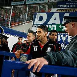 Israeli football star Abbas Suan, smiles as he enters the field during a game with his local team Bnei Sahknin at Bloomfield Stadium, Jaffa, Israel, Jan. 29, 2006. The team has a mixture of Israeli-Arab, Israeli, and foreign players. Suan, an Israeli-Arab, still faces criticism and racism resulting from the unsettled conflict between the Israelis and Palestinians.