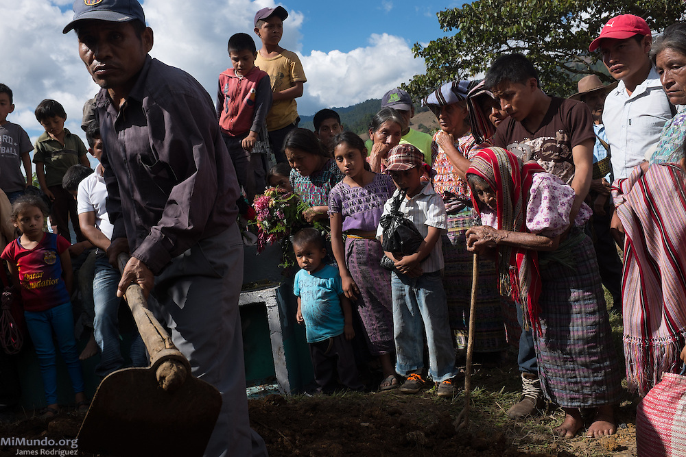 Catarina Lopez, 88, (front right, with red scarf over head) watches along with friends and family as the remains of her husband Pedro Lopez Cordoba are buried over 33 years after his execution. On February 3rd, 1982, Francisco Lopez witnessed at the Xolosinay Military Garrison in Cotzal the execution by firing squad of his father, Ixil Mayan Pedro Lopez Cordoba, who was accused by military officers of being a guerrilla sympathizer. Francisco Lopez volunteered his time to dig up trenches during the 2014 exhumations at the former Military Garrison. The remains of Lopez Cordoba, which still held an Id card with name and photo inside the pants' pocket, were exhumed by members of the Forensic Anthropology Foundation of Guatemala (FAFG) from grave 9 in September 2014 and subsequently positively identified via DNA analysis. Lopez Cordoba was returned to his family members on November 3, 2015, and buried a day later. Santa Avelina, San Juan Cotzal, Quiche, Guatemala. November 4, 2015.