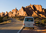 Sunset light glows orange on sandstone mesas, buttes, and pinnacles of the Windows Section of Arches National Park, Utah, USA. a Volkswagon Eurovan Camper stops at a roadside turnout.