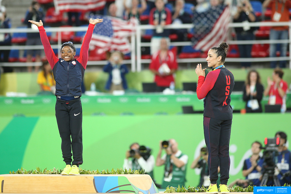 Gymnastics - Olympics: Day 6  Simone Biles of the United States on the podium at the gold medal presentation watched by silver medalist Alexandra Raisman of the United States during the Artistic Gymnastics Women's Individual All-Around Final at the Rio Olympic Arena on August 11, 2016 in Rio de Janeiro, Brazil. (Photo by Tim Clayton/Corbis via Getty Images)