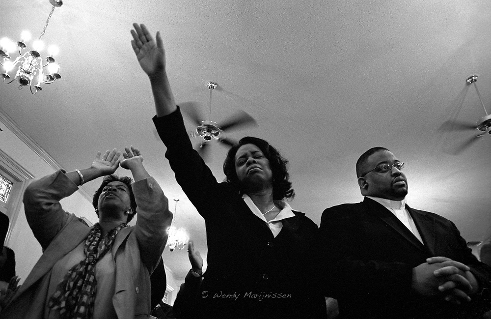 Worshippers sing and pray during a Gospel service in church. Memphis, 2004