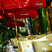 """SHOT 8/10/09 4:49:00 PM - The outside patio at Trattoria Stella East on Colfax Avenue in Denver, Co. The restaurant is very inviting with colorful chairs, stain glass in the windows in front and huge doors that open when the weather permits making the scene very bright and fun. The menu is short and sweet but offers great pizza, pasta and salads. Colfax Avenue is the main street that runs east and west through the Denver-Aurora metropolitan area in Colorado. As U.S. Highway 40, it was one of two principal highways serving Denver before the Interstate Highway System was constructed. In the local street system, it lies 15 blocks north of the zero point (Ellsworth Avenue, one block south of 1st Avenue). For that reason it would normally be known as """"15th Avenue"""" but the street was named for the 19th-century politician Schuyler Colfax. On the east it passes through the city of Aurora, then Denver, and on the west, through Lakewood and the southern part of Golden. Colloquially, the arterial is referred to simply as """"Colfax"""", a name that has become associated with prostitution, crime, and a dense concentration of liquor stores and inexpensive bars. Playboy magazine once called Colfax """"the longest, wickedest street in America."""" However, such activities are actually isolated to short stretches of the 26-mile (42 km) length of the street. Periodically, Colfax undergoes redevelopment by the municipalities along its course that bring in new housing, trendy businesses and restaurants. Some say that these new developments detract from the character of Colfax, while others worry that they cause gentrification and bring increased traffic to the area. (Photo by Marc Piscotty / © 2009)"""