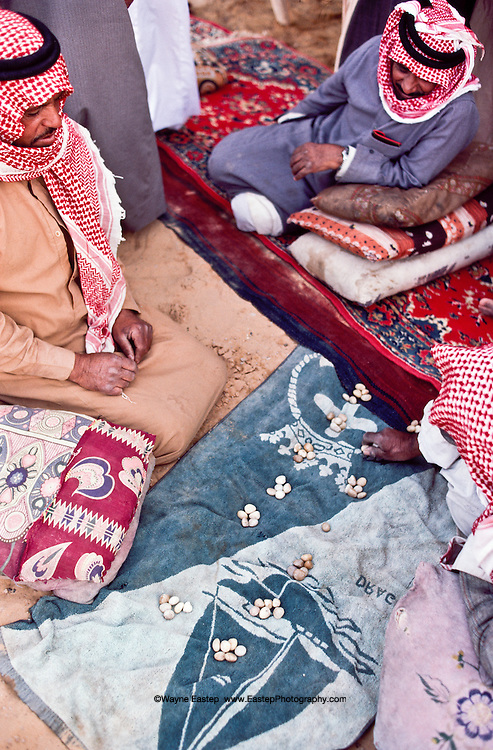 Shammar Bedouin playing a game similar to one played by the Nabataeans in Petra and Madian Saleh, similar to Mancala. Nafud, Saudi Arabia