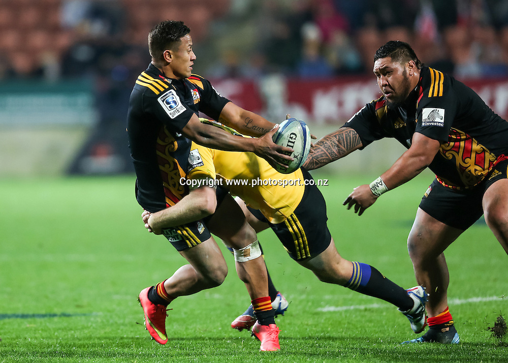 Chiefs' Tim Nanai-Williams looks to offload in a tackle from Hurricanes' Hadleigh Parkes during the Super 15 Rugby match - Chiefs v Hurricanes at Waikato Stadium, Hamilton, New Zealand on Friday 4 July 2014.  Photo:  Bruce Lim / www.photosport.co.nz