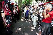 Een goth poseert voor een twee fotograferende vrouwen. In Utrecht komen goths uit heel Europa bij elkaar voor het jaarlijkse festival Summer Darkness. Tijdens het driedaags festijn zijn er onder andere optredens van bands, een markt en een modeshow. Het is ook een kwestie van zien en gezien worden.<br /> <br /> A goth is posing for two photographers at Summer Darkness. During the festival goths from all over Europe are coming to Utrecht to meet and enjoy music, a market, a fashion show and more.
