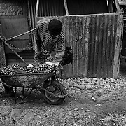The number of people affected by cholera in CitÈ Soleil, a slum of Port-au Prince,is increasing day by day exponentially, according to a doctor of Doctors Without Borders.///Jean-Pierre Britus files his mother suffering from cholera, Kernilis St John in a wheelbarrow, in the slum of Cite Soleil in Port-au-Prince, to transport her to St. Catherine's hospital in Cite Soleil.