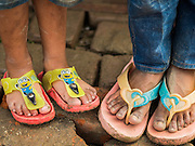 """05 AUGUST 2015 - KATHMANDU, NEPAL:  Children, one with """"Minions"""" flip flops, stand on the brick floor in their tent in a large Internal Displaced Person (IDP) Camp in the center of Kathmandu. The camp is next to one the most expensive international hotels in Kathmandu. More than 7,100 people displaced by the Nepal earthquake in April live in 1,800 tents spread across the space of three football fields. There is no electricity in the camp. International NGOs provide water and dug latrines on the edge of the camp but the domestic waste water, from people doing laundry or dishes, runs between the tents. Most of the ground in the camp is muddy from the running water and frequent rain. Most of the camp's residents come from the mountains in northern Nepal, 8 - 12 hours from Kathmandu. The residents don't get rations or food assistance so every day many of them walk the streets of Kathmandu looking for day work.     PHOTO BY JACK KURTZ"""
