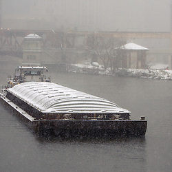 A barge heads up the North Branch of the Chicago River in a heavy snowstorm.