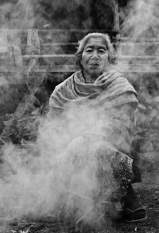 An old woman trying to keep warm during the early morning in Luang Namtha, Laos.