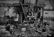 Makeshift houses of migrants from Surigao, Mindanao living in Parola slum, which sits on reclaimed land at the mouth of the Pasig River, the main river running through Manila.  This settlement is extremely vulnerable to floods, typhoons, sewage and industrial contamination carried down Pasig.  Tondo, Manila, Philippines.<br /> <br /> On Maplecroft's Climate Change Vulnerability Index, Manila ranks as the world's second most vulnerable city to climate change.  Manila's Tondo is Manila's district most vulnerable to climate change-induced sea rises, storm surges from increasingly strong typhoons and earthquake trigger tsunami.  It has a population density of nearly 78,000 people per square km (202,800 ppl/sq mi), according to a 2009 Cornell University report.  (Note: Manhattan has a population density of 26,939/km2 [69,771/sq mi].)