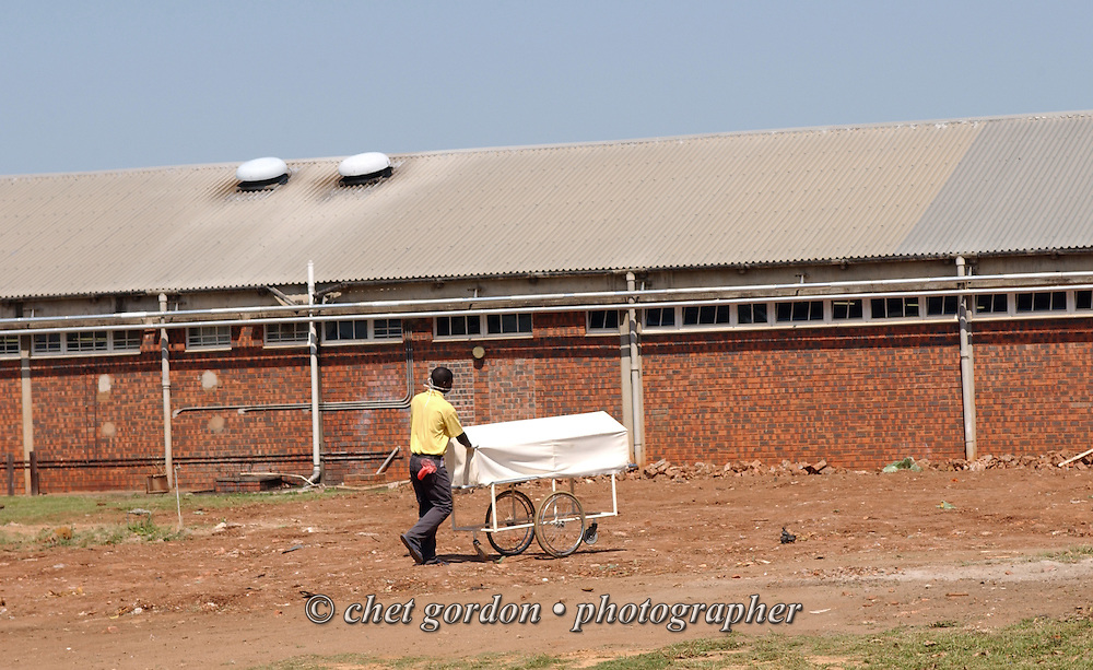 EMPANGENI, SOUTH AFRICA.  A hospital worker transports a body on the grounds of the Ngwelezana Hospital in Empangeni, South Africa on September 9, 2006.    © www.chetgordon.com