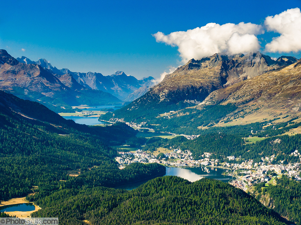 """St. Moritz and three lakes nestle in Upper Engadine Valley. See Lake St. Moritz (Lej da San Murezzanor or St. Moritzer See), Lake Sils (Lej da Segl, famous for windsurfing), Lake Silvaplana (Lej da Silvaplauna), and Maloja mountain pass. Visit Graubünden canton, Grison Alps, Switzerland, Europe. Reach Muottas Muragl viewpoint by funicular railway from a train station between Samedan-St. Moritz and Pontresina on the Bernina Express line. The Swiss valley of Engadine translates as the """"garden of the En (or Inn) River"""" (Engadin in German, Engiadina in Romansh, Engadina in Italian). Published in Ryder-Walker Alpine Adventures """"Inn to Inn Alpine Hiking Adventures"""" Catalog 2006."""