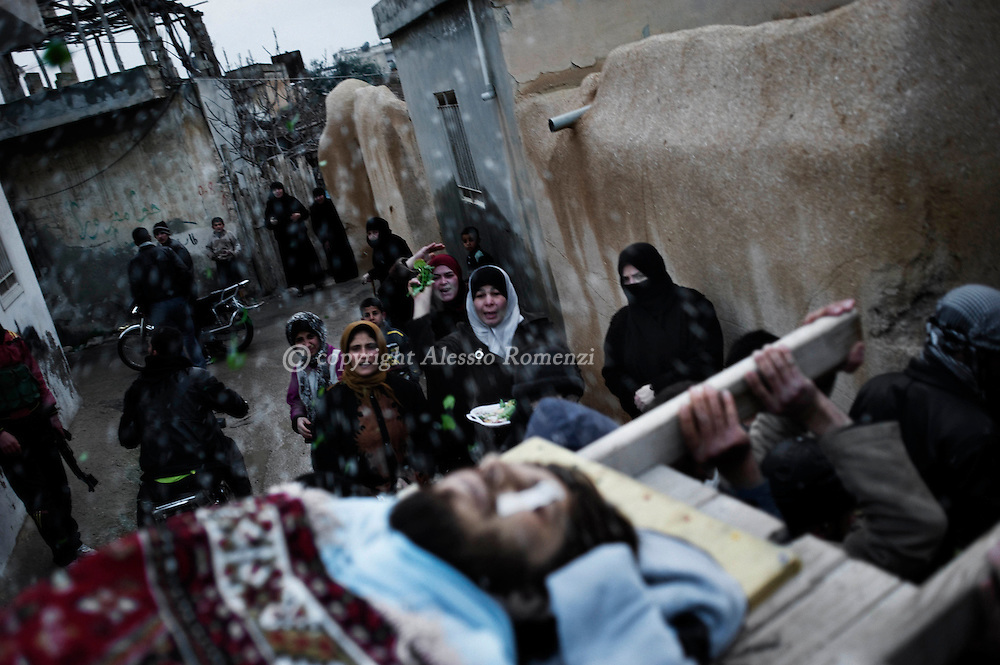 SYRIA - Al Qsair. Mourners throw leaves and rice at the coffin of Asem Bader Waw, 31 y.o., shot dead by a Syrian Army's sniper on January 31, 2012. Al Qsair is a small town of 40000 inhabitants, located 25Km south-west of Homs. The town is besieged since the beginning of November and so far it counts 65 dead. ALESSIO ROMENZI