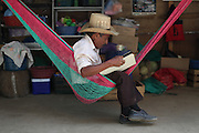 """Lorenzo Catalan, 80, from La Choleña, takes a break by looking at a book. """"I can not read, but I enjoy looking at the photos of these animals while I'm here on duty. The 24 hours shifts from 5 PM to 5 PM are long and unfortunately one does get bored at times.""""  Since March 2nd, 2012, local neighbors from San José del Golfo and San Pedro Ayampuc have blocked the entrance to the EXMINGUA gold mine - owned by Kappes, Cassiday & Assocaites (KCA) based in Reno, Nevada, USA. Residents from the communities claim the industrial activity in their territories as illegal since they were not appropriately consulted before the mine began operating. La Puya, San Pedro Ayampuc, Guatemala. May 14, 2013."""
