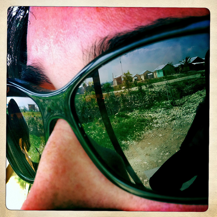 The Corail camp is reflected in sunglasses on Monday, April 2, 2012 in Port-au-Prince, Haiti.