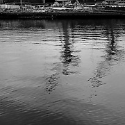 Cranes from a shipbuilding yard are seen reflected in the River Clyde, in Glasgow Scotland where shipbuilding was once a major industry. Large quantities of asbestos were used in building ships in the past resulting in numerous cases of asbestos related cancers, asbestosis and deaths.