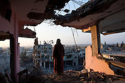 A Palestinian woman overlooks the destruction in Shujayea at dawn Aug. 8, 2014. On Friday the 72 hour cease fire came to an end without a longer term agreement . Rockets fired by Palestinian militants hit Israel and Israel resumed its air strikes .(Photo by Heidi Levine/Sipa Press).