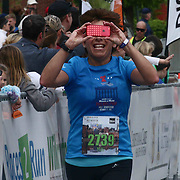 Milena Crippa (2739) of Avondale, PA., takes a photo as she approaches the finish line during the 13th Annual Discover Bank Delaware Marathon Sunday, May 8, 2016, at Tubman Garrett Riverfront Park, in Wilmington Delaware.