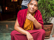 31 JULY 2015 - KATHMANDU, NEPAL:  A Tibetan Buddhist monk at a monastery near Bodhnath Stupa. Bodhnath Stupa in the Bouda section of Kathmandu is one of the most revered and oldest Buddhist stupas in Nepal. The area has emerged as the center of the Tibetan refugee community in Kathmandu. On full moon nights thousands of Nepali and Tibetan Buddhists come to the stupa and participate in processions around the stupa. The stupa was heavily damaged in the earthquake of 25 April 2015 and people are no longer allowed to climb on the stupa, now they walk around the base and pray with butter lamps.  PHOTO BY JACK KURTZ