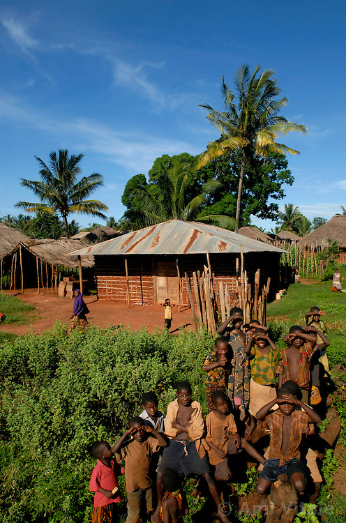 Villagers watch as lion researcher Dennis Ikanda and trapper Dairen Simpson look for lion prints in Navanga, Tanzania. The dense forest and tall grasses make villagers vulnerable to lion attacks. They have to stay late in the evening in their fields to protect their crops from rampaging monkeys who like to eat the rice and corn, forcing them to walk at sunset, the time of day when lions are out looking for prey.  Ami Vitale