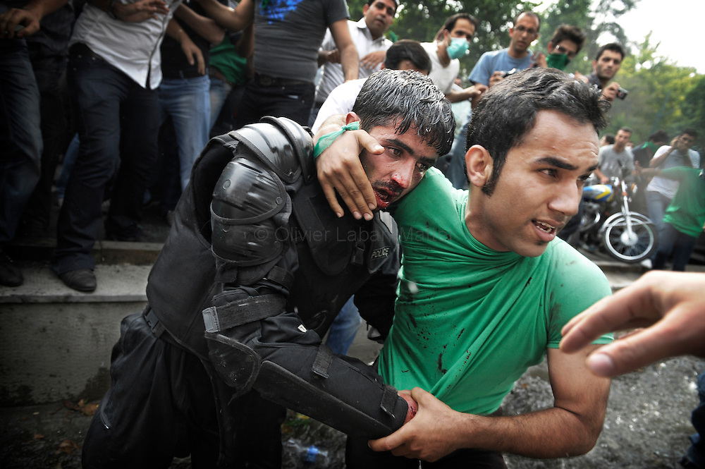 A supporter of defeated Iranian presidential candidate Mir Hossein Mousavi helps evacuate an injured Iranian riot-police officer during riots in Tehran on June 13, 2009. Hardline incumbent Mahmoud Ahmadinejad won a crushing victory in Iran's hotly-disputed presidential vote, according to official results that triggered mass opposition protests.