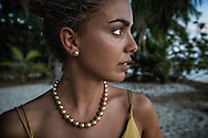 Young woman wearing a necklace of golden pearls by Jewelmer at Flower Island Resort on Large Bulucan Island.  Shark Fin Bay, Palawan, Philippines.