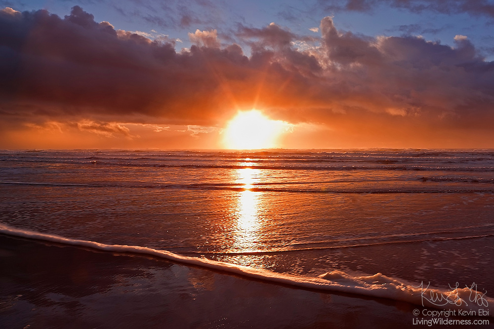 The setting sun breaks through storm clouds over the Pacific Ocean near Manzanita, Oregon.