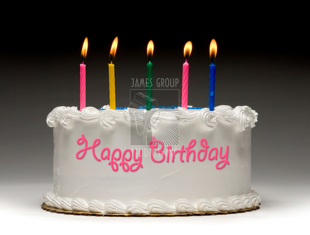 """White birthday cake profile on graident background with five colorful lit candles and """"Happy Birthday"""" written on the side with frosting"""