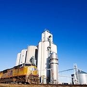 Speeding east on the extremely busy Union Pacific mainline through Nebraska, a freight train passes the tall grain elevators in Elm Creek, NE.