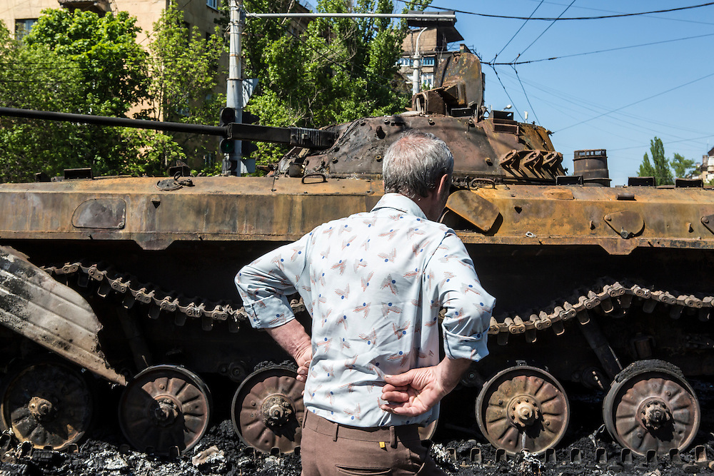 MARIUPOL, UKRAINE - MAY 10: A man inspects a burned tank a day after deadly clashes on May 10, 2014 in Mariupol, Ukraine. A referendum on greater autonomy is planned for the region tomorrow. (Photo by Brendan Hoffman/Getty Images) *** Local Caption ***