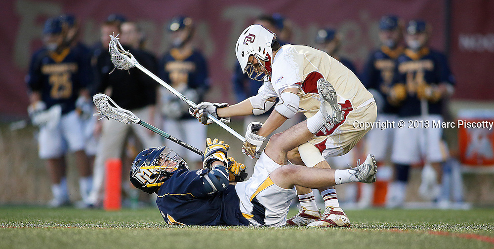 SHOT 4/5/13 6:23:00 PM - Marquette's K.C. Kennedy #11 is knocked to the ground by a University of Denver player during their NCAA Men's Lacrosse game at the Peter Barton Lacrosse Stadium on the school's campus. The University of Denver won the game 15-4.(Photo by Marc Piscotty / © 2013)