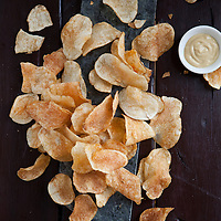 Billy Goat brand potato chips (St. Louis, MO) scattered on a table with a small dish of mustard.