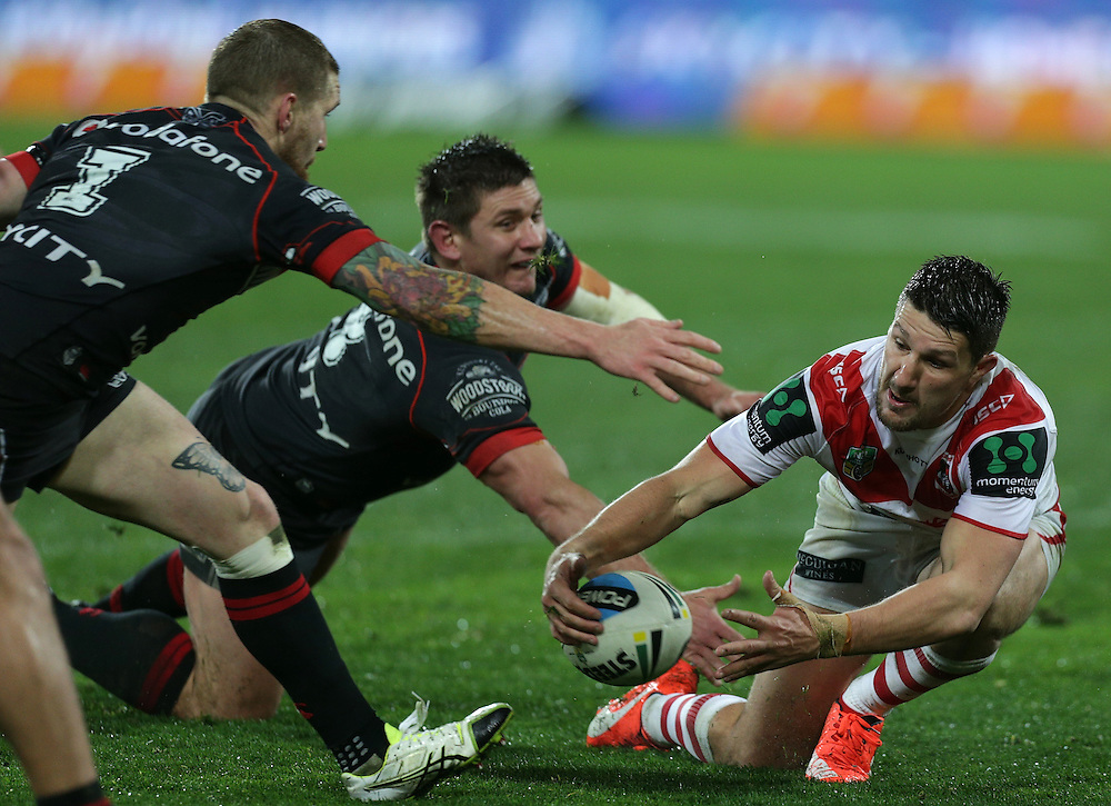 Gareth Widdop of the Dragons is challenged by Sam Tomkins, left, and Jacob Lillyman of the New Zealand Warriors during their round 22 NRL match at Westpac  Stadium, Wellington on  Saturday, August 08, 2015. Credit: SNPA / David Rowland