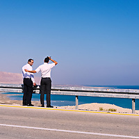 Tourists stand on the shoulder of Highway 90 overlooking the Dead Sea.