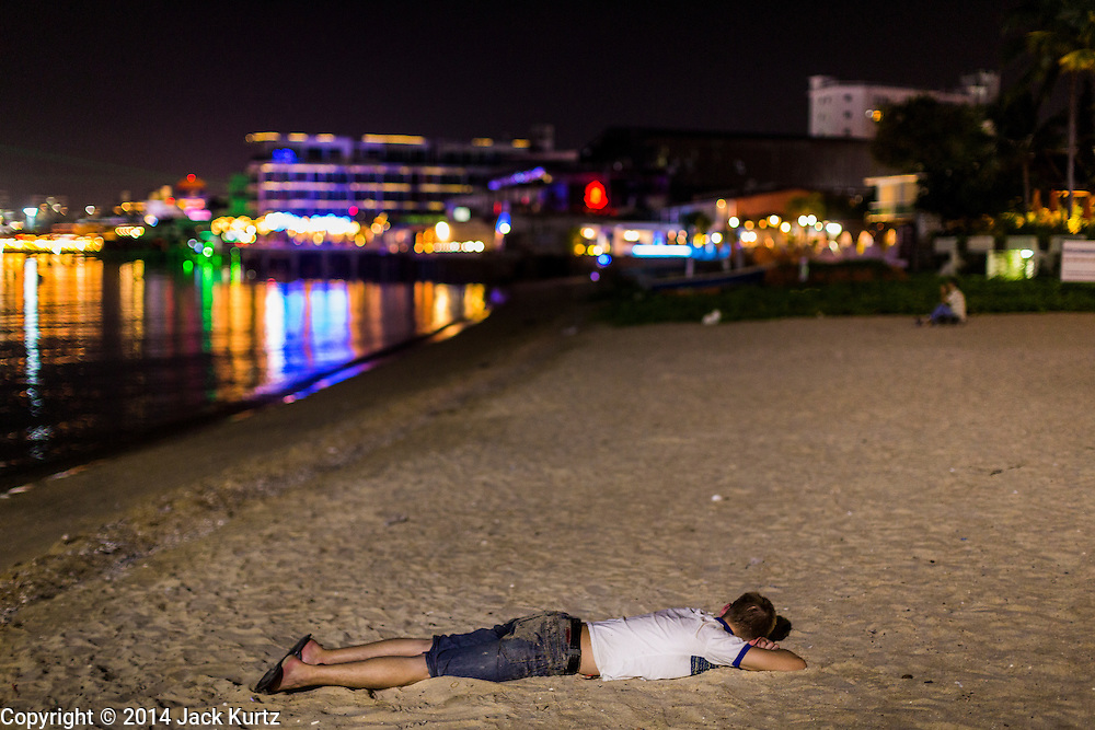 "26 SEPTEMBER 2014 - PATTAYA, CHONBURI, THAILAND: A tourist lies on the sand, passed out on Pataya Beach. Pataya, a beach resort about two hours from Bangkok, has wrestled with a reputation of having a high crime rate and being a haven for sex tourism. After the coup in May, the military government cracked down on other Thai beach resorts, notably Phuket and Hua Hin, putting military officers in charge of law enforcement and cleaning up unlicensed businesses that encroached on beaches. Pattaya city officials have launched their own crackdown and clean up in order to prevent a military crackdown. City officials have vowed to remake Pattaya as a ""family friendly"" destination. City police and tourist police now patrol ""Walking Street,"" Pattaya's notorious red light district, and officials are cracking down on unlicensed businesses on the beach.     PHOTO BY JACK KURTZ"