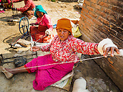 01 MARCH 2017 - KHOKANA, NEPAL: A woman spins wool to make blankets in Khokana. Recovery seems to have barely begun nearly two years after the earthquake of 25 April 2015 that devastated Nepal. In some villages in the Kathmandu valley workers are working by hand to remove ruble and dig out destroyed buildings. About 9,000 people were killed and another 22,000 injured by the earthquake. The epicenter of the earthquake was east of the Gorka district.     PHOTO BY JACK KURTZ