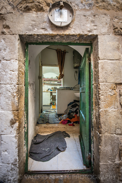 The entrance of a Palestinian house in Hebron. The Kitchen is visible on the back; a pile of clothes is ammassed under a sink. The Israely army routinely raids Arab's homes leaving behind chaos, rarely finding anything.