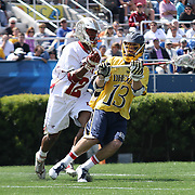 Drexel Midfielder Ryan Belka (13), RIGHT, position himself towards the goal as Denver Midfielder Terry Ellis (12), LEFT, defends in the second half of The NCAA Division I Men's Lacrosse Tournament game between the No. 5 seed Denver and No. 12 ranked Drexel Sunday, May. 18, 2014 at Delaware Stadium in Newark, DEL