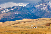 Pumpjack at oil well on the Montana plains near the Rocky Mountain Front Ranges of Glacier National Park USA