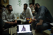 Syria. Sheik Tawfiq and members of the Free Syrian Army are discussing and making plans for next moves of their armed group as on the screen is running the video of the interview to a shabbiah precedently captured and after released because judjed innocent. ALESSIO ROMENZI