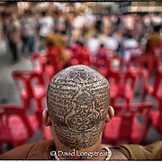 """In this """"Signature Series"""" image by David Longstreath, a young Buddhist Monk displays his tattoos at the annual tattoo festival at Wat Bang Pra in Chong Nasi, Thailand."""