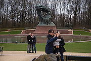 Visitors at the Fryderyk Chopin Monument in Łazienkowski Park, Warsaw.