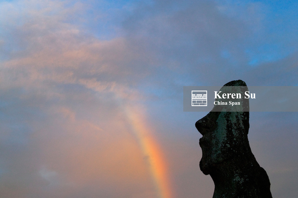 A lone Moai (volcanic stone sculptures) with rainbow at Ahu Tongariki, Easter Island, Chile