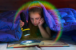 Girl reading book in bed under blanket. Dark room, kid holding flashlight, lamp.
