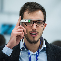 London, UK - 17 March 2014:  a visitor wears smart glasses at the Wearable Technology Conference at Olympia in London